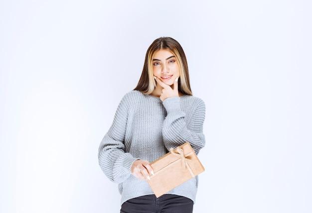 Mädchen erhielt eine geschenkbox aus karton von einem unbekannten absender und dachte nach.