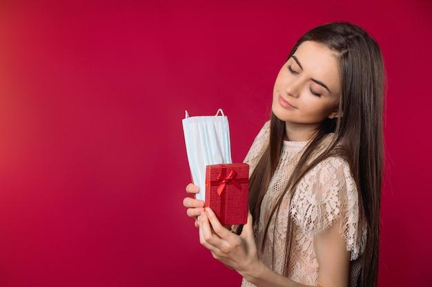 Mädchen erhielt eine medizinische maske als geschenk auf rotem hintergrund mit leerzeichen