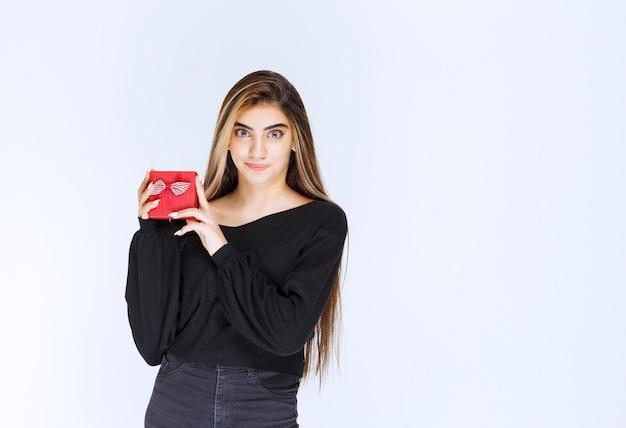 Mädchen erhielt eine rote geschenkbox und fühlte sich glücklich. foto in hoher qualität