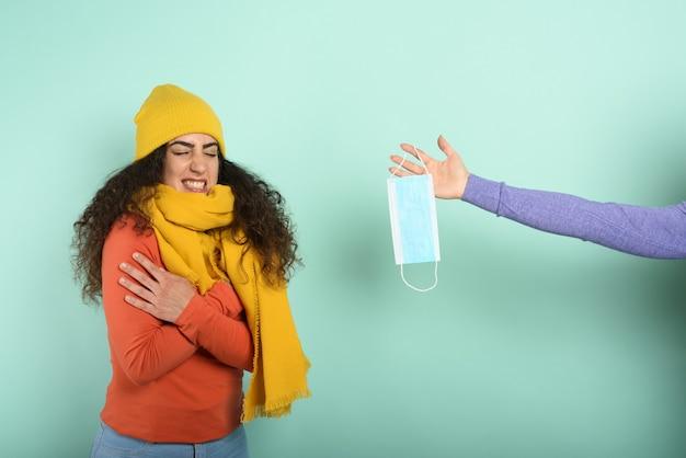 Mädchen erkältet und jemand gibt ihr eine maske. violette wand