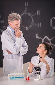 Mädchen erklärt dem doktor, was sie im labor tut.