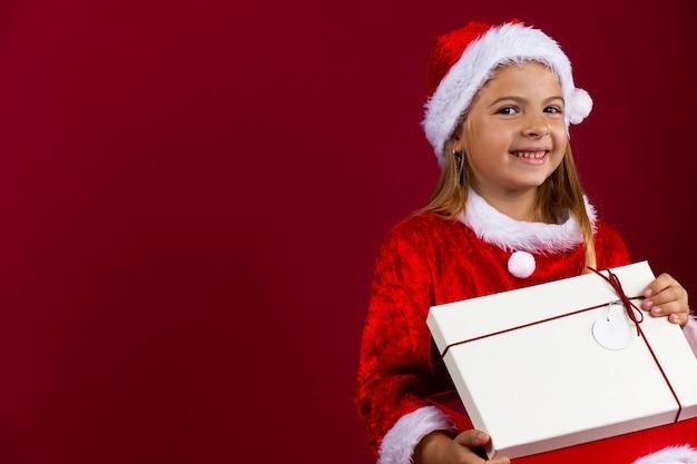 Mädchen eröffnungsgeschenk. porträt eines hübschen kleinen mädchens, das weihnachtsmann-outfit trägt und lächelt. kaukasisches kleines babygirl. rote isolierte wand.