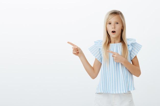 Mädchen erstaunt, zaubertrick zu sehen. porträt einer faszinierten, bewundernden jungen blonden tochter in einer trendigen blauen bluse, die wow sagt, mit dem zeigefinger nach links zeigt, sich erstaunt fühlt und über die graue wand schnappt
