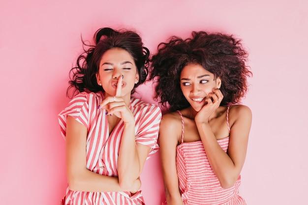 Mädchen erzählt klatsch zu ihrer freundin und bittet sie zu schweigen, den finger vor den mund zu legen. mulattenfrau, die ihren cousin geschockt ansieht.