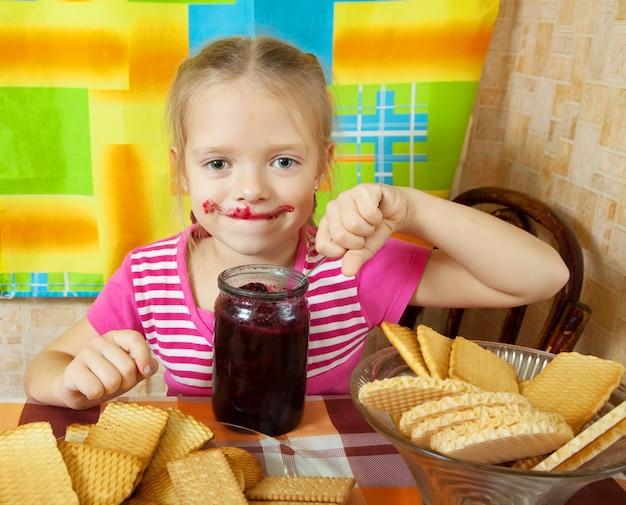 Mädchen essen marmelade aus glas