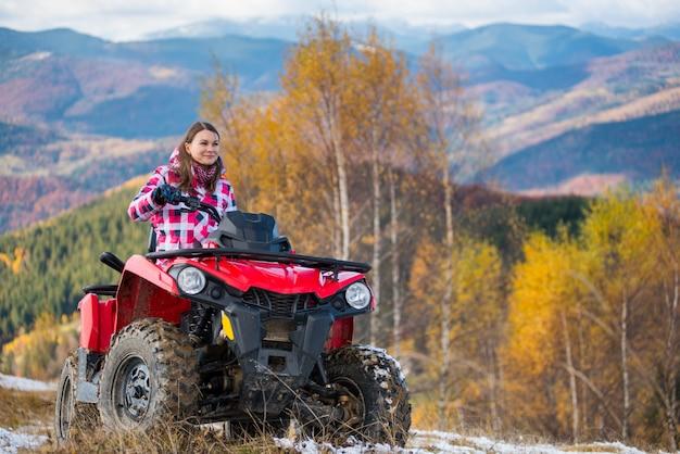 Mädchen fährt ein quad auf einer schneebedeckten straße