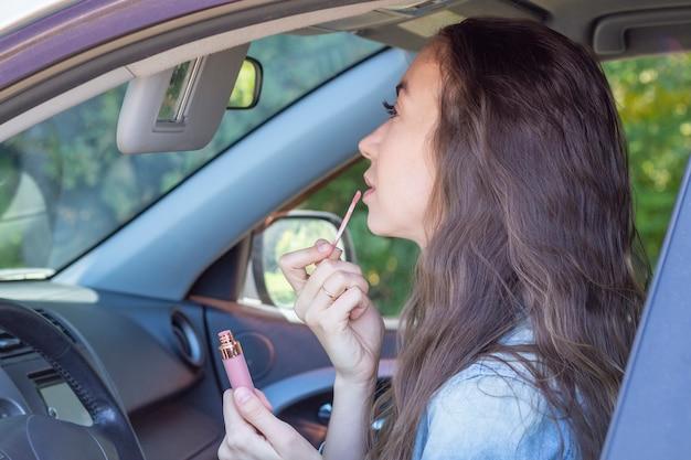 Mädchen fährt ihr auto, malt ihre lippen und schaut in den autospiegel. fahrer frau