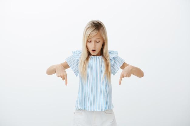 Mädchen fasziniert und aufgeregt beim gehen auf glasboden. porträt der verblüfften attraktiven blonden kleinen tochter in der niedlichen blauen bluse, die mit gesenktem kiefer zeigt und nach unten schaut und über graue wand steht