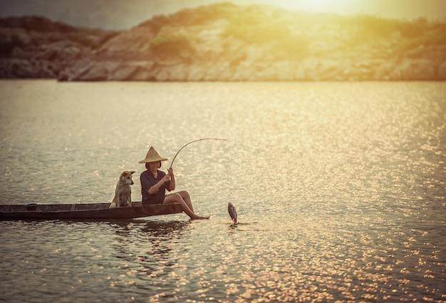 Mädchen fischt auf boot mit ihrem hund