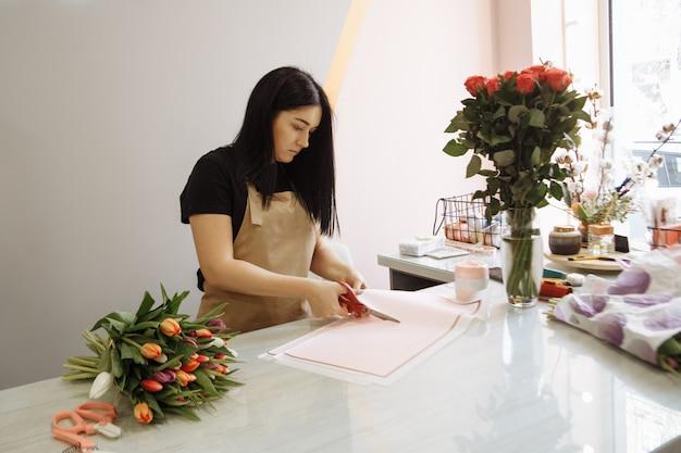 Mädchen florist mit schere verziert einen blumenstrauß tulpen in einem blumenladen