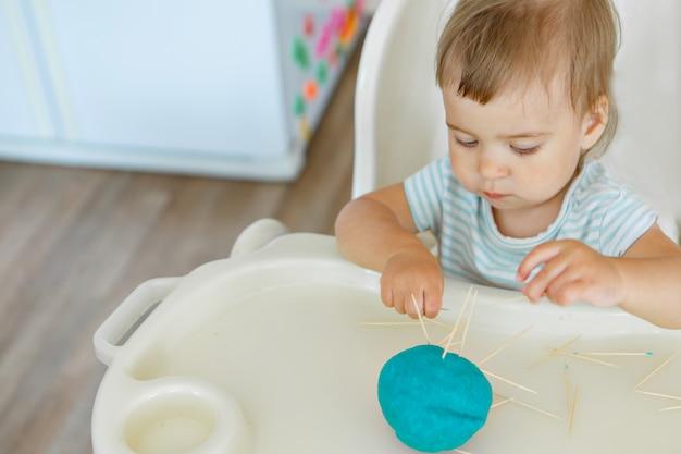 Mädchen formt aus plastilin. ein kind macht ein igelhandwerk.