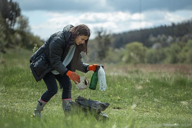 Mädchen-freiwillige sammelt müll im wald, kümmert sich um die umwelt.