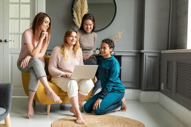 Mädchen freundschaft online-shopping-konzept. vier schöne freunde sitzen zu hause und bestellen über das internet.