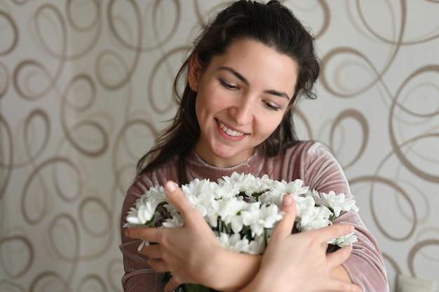 Mädchen freut sich über einen strauß weißer blumen. brünette umarmungen schnüffeln einen strauß zarter blumen von ihrer geliebten. ein gutes geschenk für ihre geliebte hälfte.