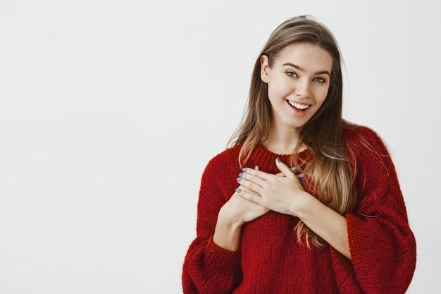 Mädchen freut sich über komplimente von corowker im büro. berührt charmantes europäisches weibliches modell im stilvollen roten losen pullover, hält handfläche auf brust und lächelt vor zufriedenheit über graue wand