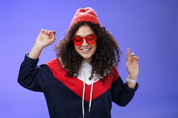 Mädchen fühlen sich großartig, haben spaß und genießen eine coole party, tanzen mit erhobenen händen und schauen nach unten und lächeln breit mit sonnenbrille und stylischer mütze, die vor blauem hintergrund posiert.