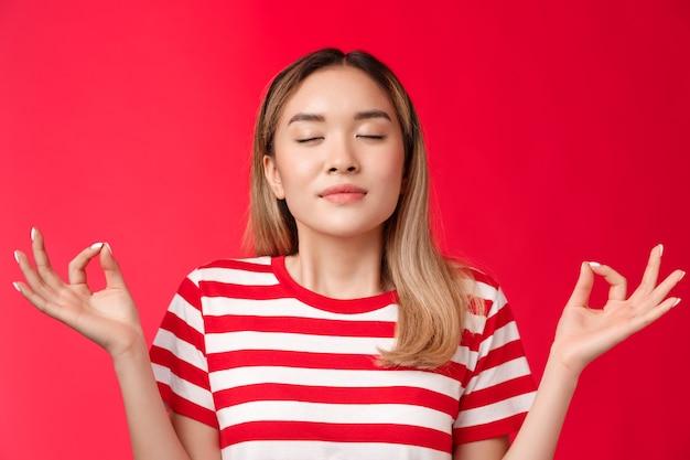 Mädchen fühlen zen süßes asiatisches mädchen, das meditiert, vereinen sich mit der natur enge augen atmen tief halten hände r ...