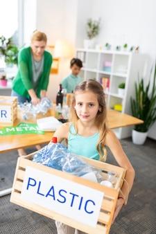 Mädchen fürsorgliche box. nette schöne mädchen-pflegebox mit kunststoff nach der abfallsortierung mit klassenkameraden in der schule