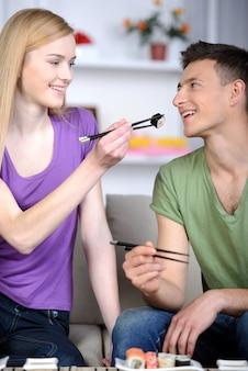 Mädchen füttert einen mann mit sushi zu hause.