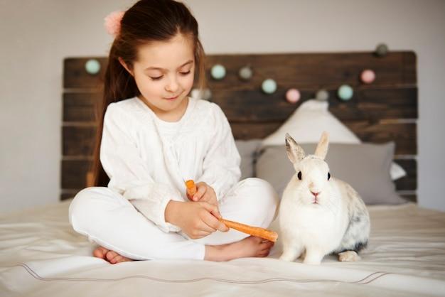 Mädchen füttert ihr kaninchen auf dem bett