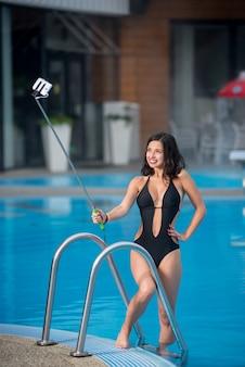 Mädchen gegen schwimmbad macht selfie foto