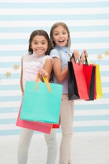 Mädchen gehen gerne shoppen. kinder glückliche kleine mädchen halten einkaufstaschen. viel spaß beim einkaufen mit der besten freundin oder schwester. mädchenhaftes glück. kinder tragen gerne bündelpakete. einkaufen mit dem konzept des besten freundes.