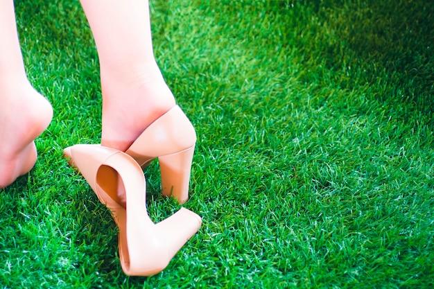 Mädchen geht auf das gras und verliert einen schuh