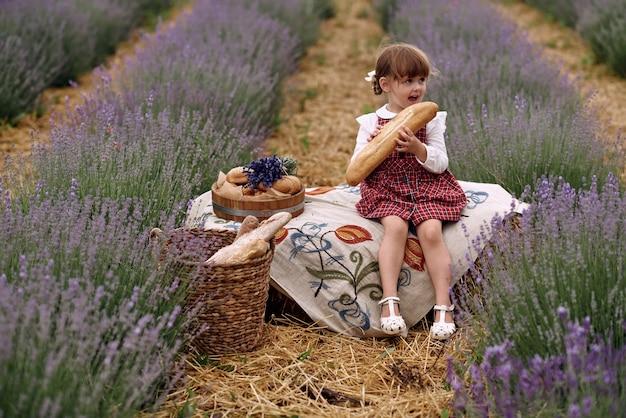 Mädchen geht auf einem lavendelfeld blumen sammeln. Premium Fotos