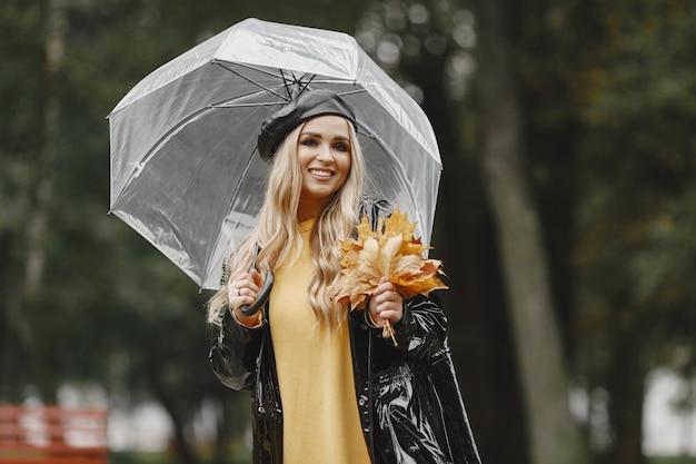 Mädchen geht. frau in einem schwarzen mantel. blond mit schwarzer mütze. dame mit regenschirm.