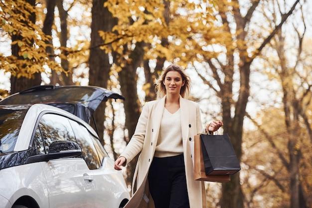 Mädchen geht mit einkaufstüten in den händen in der nähe des autos. modernes brandneues auto im wald.
