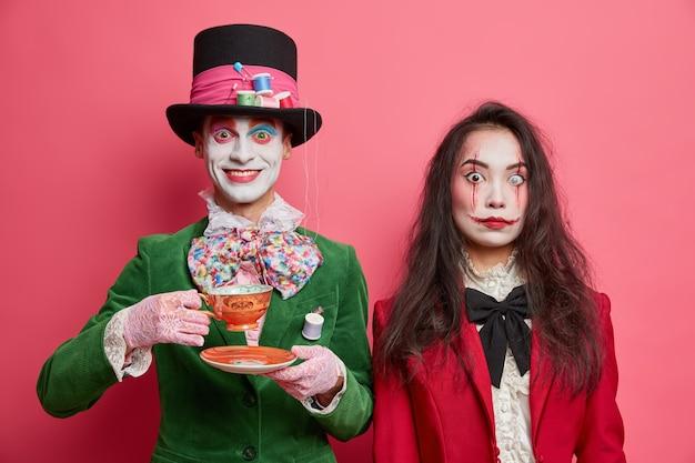 Mädchen geist hat gruseliges make-up und erfreut verrückten hutmacher im kostüm trinkt tee auf party