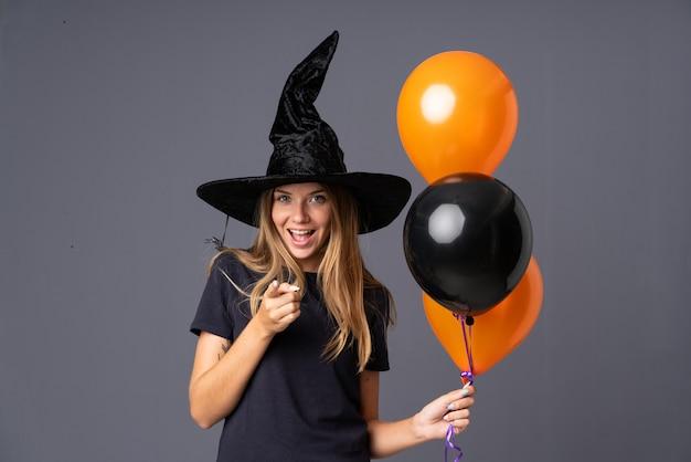 Mädchen gekleidet als hexe für halloween und auf die front zeigend