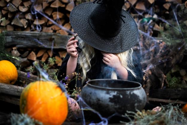 Mädchen gekleidet als hexe, schwarzer hut, langes weißes haar, schwarze spinne, halloween-feiertag
