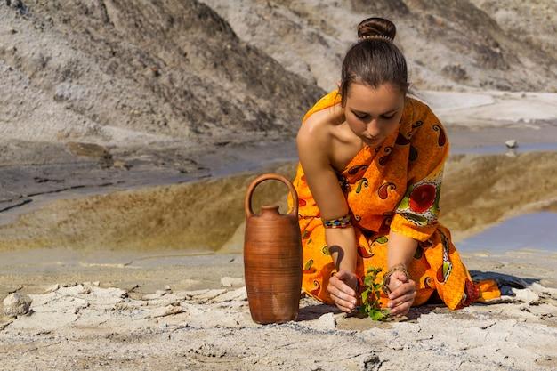 Mädchen, gekleidet in einem traditionellen sari in der wüste, das versucht, vor einer dürre einsamen sprössling zu retten?