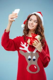 Mädchen gekleidet in weihnachtsmütze mit einem weihnachtsgeschenk und telefon