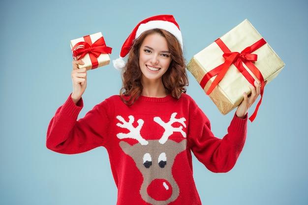Mädchen gekleidet in weihnachtsmütze mit weihnachtsgeschenken
