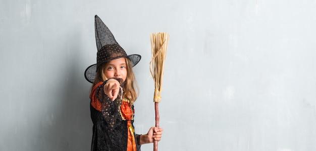 Mädchen gekleidet wie eine hexe und einen besen für halloween-feiertage halten, die auf die front zeigen