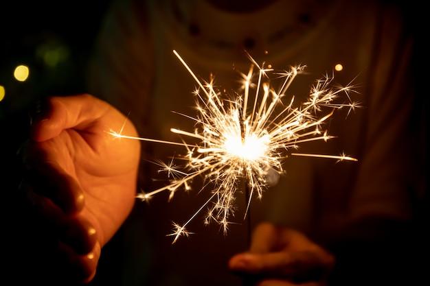 Mädchen genießen, mit einem kleinen wunderkerzenhandfeuerwerk zu spielen