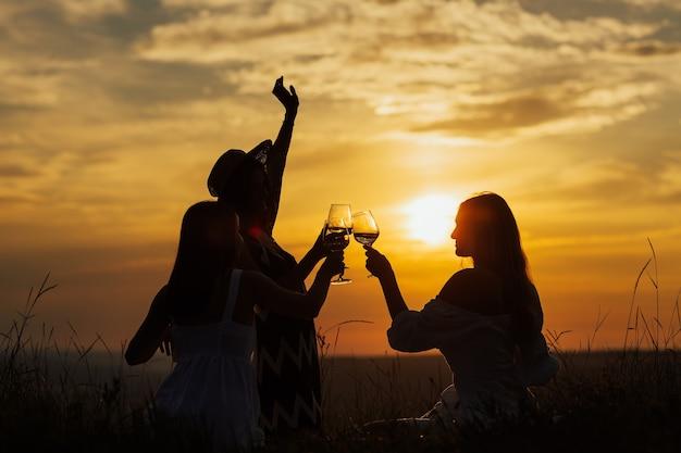 Mädchen genießen picknick neben dem fluss. junge freunde, die spaß am hügel nach sonnenuntergang haben.