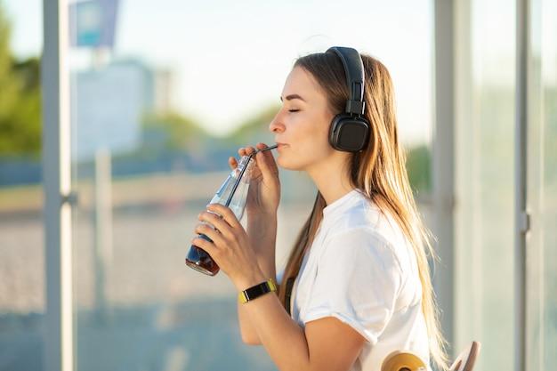Mädchen genießen, soda in hörender musik zu trinken