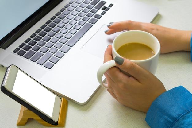 Mädchen genießt einen laptop und trinkt kaffee. smartphone auf einem ständer