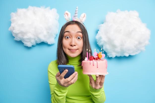 Mädchen genießt geburtstagsfeier postet fotos in sozialen netzwerken hält kuchen mit brennenden kerzen sieht beeindruckt aus, gekleidet in freizeitkleidung isoliert auf blau