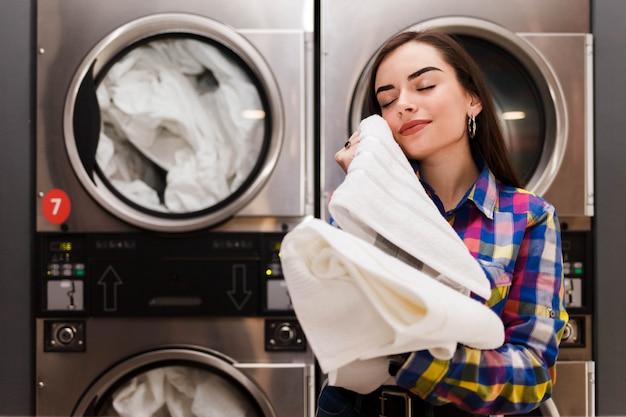 Mädchen genießt saubere und riechende handtücher nach dem waschen im waschsalon