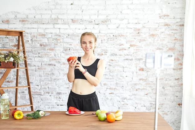 Mädchen gesunde blogger zeigt fruchtige und saubere diätnahrung. vlogger zeichnet live-streaming zu hause auf