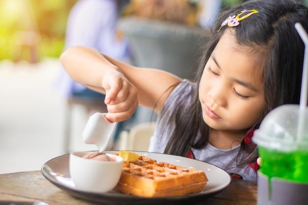 Mädchen gießen süßen honig sirup