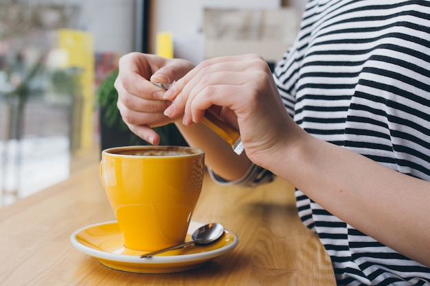 Mädchen gießt zucker aus einer tüte in eine tasse kaffee