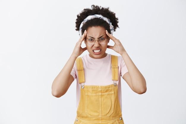 Mädchen glaubt, dass sie objekt mit geisteskraft bewegen kann. porträt der lustigen und wütenden niedlichen frau in latzhose, stirnband und brille, stirnrunzeln und zusammengebissene zähne mit wut, finger auf der stirn haltend