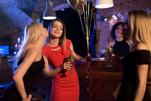 Mädchen gratulieren ihrer freundin zu ihrem geburtstag, während sie das ereignis im nachtclub feiern