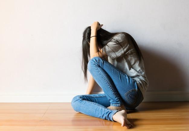 Mädchen haben angst, auf weißem hintergrund zu sitzen