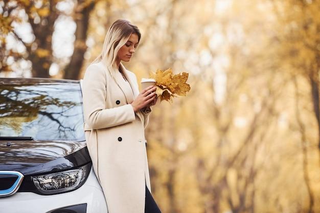Mädchen haben eine herbstreise mit dem auto. modernes brandneues auto im wald.